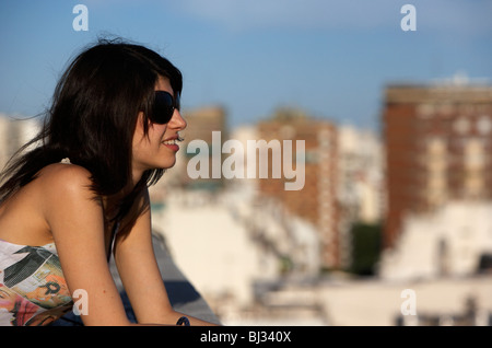 young hispanic latin woman looking out over city buenos aires - Stock Photo