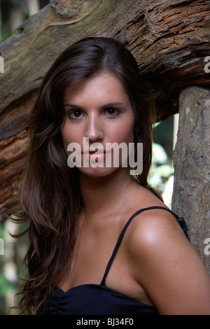 young hispanic latin woman in evening dress leaning against a tree looking angry in a forest in argentina south - Stock Photo