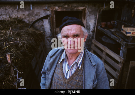 Dressed in typical overalls for the area, traditional Alpine farmer Peter Eberle in the courtyard of his small farm. - Stock Photo