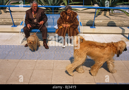 An elderly and eccentric couple sit on a park bench in the French Mediterranean resort of Juan-les-Pins near Antibes. - Stock Photo