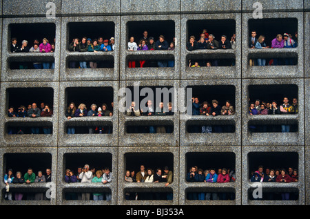 Londoners gather on three levels of a multi-story car park to await athletes pass during the London Marathon. - Stock Photo