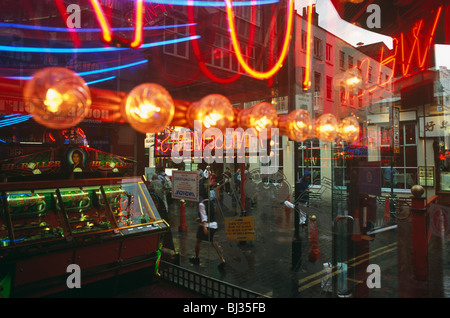 Tthrough the window of an amusement arcade in London's Gerrard Street, Chinatown, we see colourful neon lights and - Stock Photo