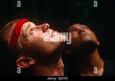 In tropical heat, two young men adventurers gaze up to the rainforest canopy during Raleigh International expedition - Stock Photo