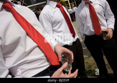 City of London office workers gather to drink at lunchtime while dressed in red ties and white shirts on St George's - Stock Photo