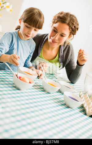 mother and child coloring Easter eggs - Stock Photo