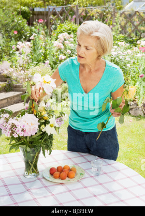 mature woman arranging flowers in vase. - Stock Photo