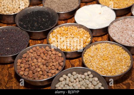 India, Kerala, Calicut, Kozhikode, Halwa Bazaar, plates of different dried pulse samples on display in food wholesaler - Stock Photo