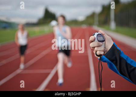 2 female athletes and stopwatch - Stock Photo