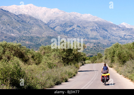 Cyclist on a road overlooking the White Mountains, Lefka Ori, near Vamos, Crete, Greece, Europe - Stock Photo