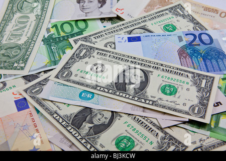 A mixture of bank notes, U.S. dollars, euros and British pounds - Stock Photo