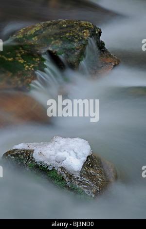 Flowing movement, close-up with snow, ice, Kleine Ohe mountain stream, Nationalpark Bayrischer Wald Bavarian Forest - Stock Photo