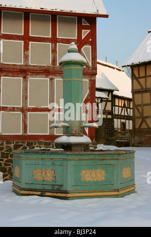 Village well and half-timbered houses in snow, winter in the Freilichtmuseum Hessenpark open air museum, Neu-Anspach, - Stock Photo
