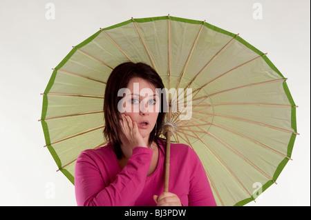 portrait of beautiful teenage girl with green umbrella
