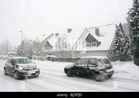 Two cars on a village road in a heavy snow flurry - Stock Photo