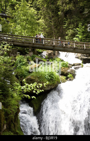 Triberg, bridge with tourists above one of the highest waterfalls in Germany - Stock Photo