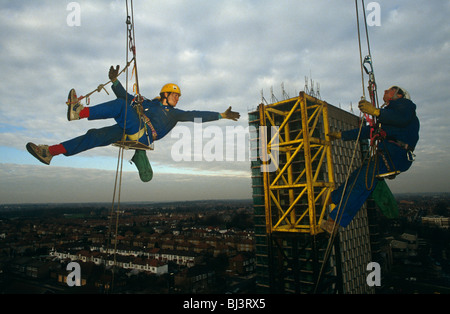 High above the skyline of North London member of a company of abseiling construction scaffold workers make use of - Stock Photo