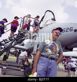 A visitor to Oshkosh Air Venture, the world's largest air show in Wisconsin USA, stands by an A-10 Thunderbolt tank - Stock Photo