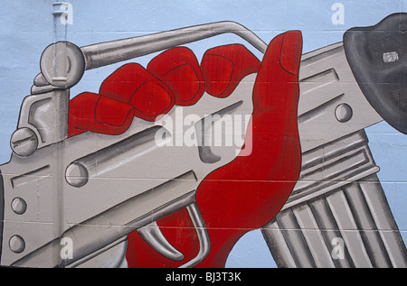 Apainted red hand that grips an Armalite automatic weapon which has been painted on to a street wall of a Belfast - Stock Photo
