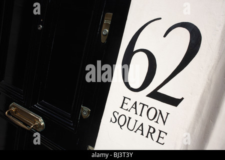 A detail of number 62 in London's famous Eaton Square complete with heavy gloss-painted black door. - Stock Photo