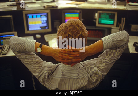 A young trader in currencies leans back in his chair on the currency trading floor of Barclays Bank - Stock Photo
