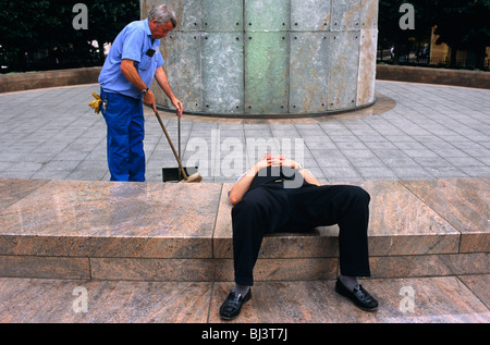 A street sweeper nearby brushes away litter with a small dustpan near sleeping office white-collar worker. - Stock Photo