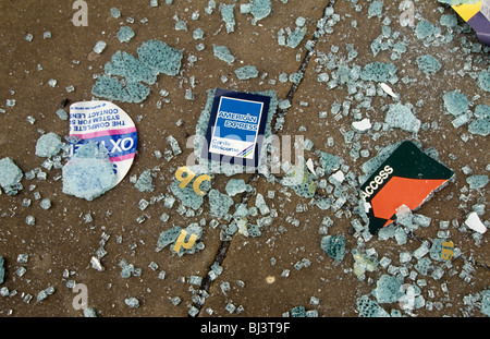 Access (Mastercard) and American Express (Amex) credit cards lie on the disaster-strewn pavement, aftermath of an - Stock Photo