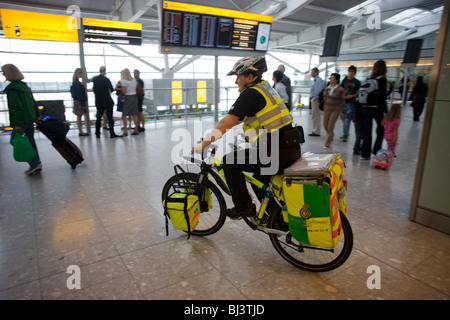 NHS Paramedic Janet Greenhead cycles through the departures concourse on her Specialized Rockhopper mountain bike - Stock Photo
