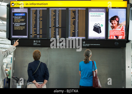 Departures information board at Heathrow Airport's Terminal 5 is viewed by passengers who stands motionless. - Stock Photo
