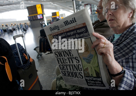 Two elderly but travel-wise passengers read the Daily Mail newspaper while awaiting their check-in zone at Heathrow - Stock Photo