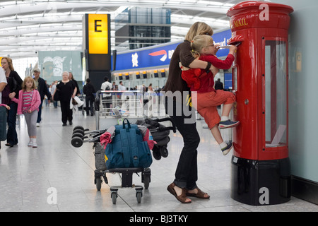 Young mother holds up her daughter to insert a letter into a post box at Heathrow Airport's Terminal 5. - Stock Photo