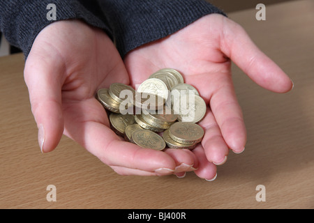Female hands holding some English pound coins. - Stock Photo
