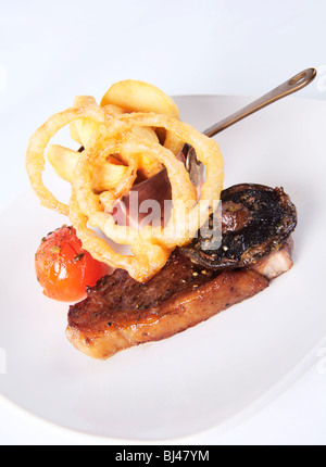 Fried Sirloin Steak with Chips and Tempura Batter Onion Rings - Stock Photo