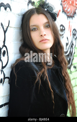 young goth woman posing in front of graffiti - Stock Photo