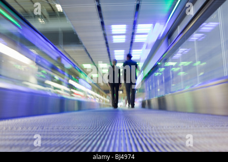 conveyor belt with couple in background - Stock Photo