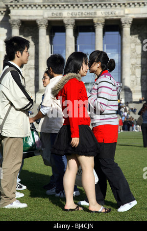 Young Asian tourists in front of the Reichstag, Berlin, Germany - Stock Photo