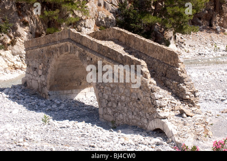 An old bridge from the Roman period spans the dry river bed in the Samaria Gorge in Agia Roumeli, Crete, Greece, - Stock Photo