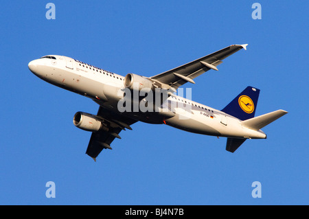Airbus A320 operated by Lufthansa climbing out from take off at London Heathrow Airport - Stock Photo