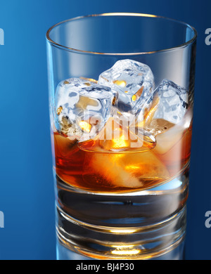 Glass of brandy with ice cubes isolated on a blue - Stock Photo