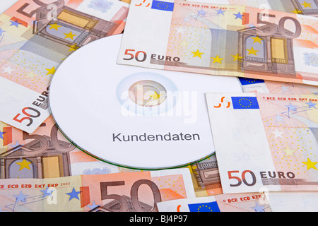 CD labelled 'Kundendaten', German for 'customer data', 50 euro notes, symbolic image for illegal trade with customer - Stock Photo