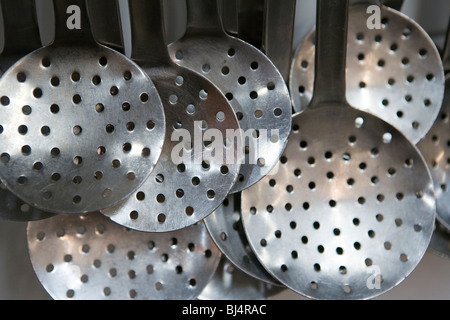 Skimming ladles in a commercial kitchen - Stock Photo