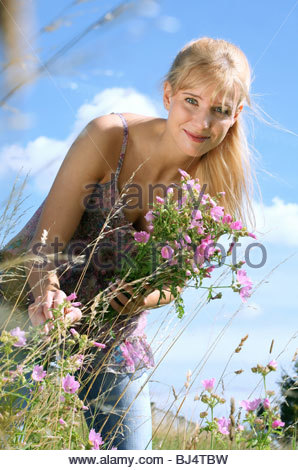portrait young blond woman  walking through greenfield holding a bunch of mallows - Stock Photo