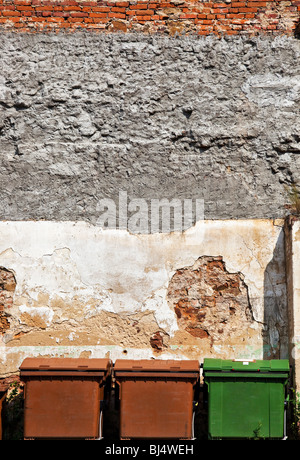 Three refuse bins on wall background. - Stock Photo