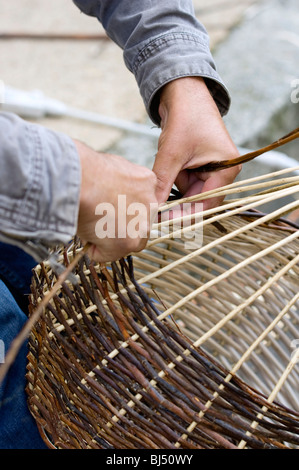 A basket weaver sitting on the street and weaving a basket, Brittany, France, Europe - Stock Photo