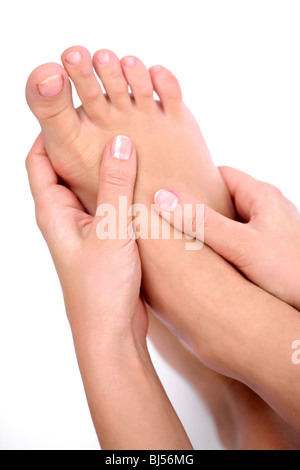 Young woman massages her foot. On a white background. - Stock Photo