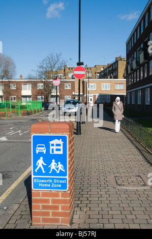 UK Muslim woman walking in the Stapleton House council housing estate in Tower Hamlets London - Stock Photo