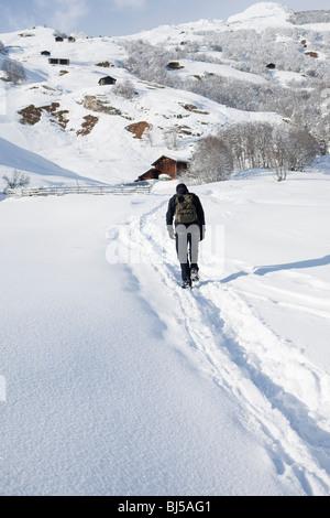 Man walking through snow in countryside - Stock Photo