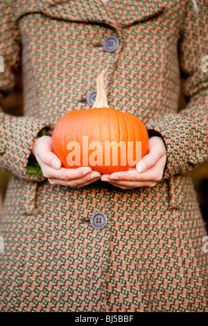 Woman with a pumpkin in her hands - Stock Photo