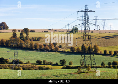 Pylons striding across the Cotswold countryside near Cassey Compton, Gloucestershire - Stock Photo