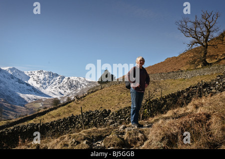 Woman stops to look at view on circular walk from Elterwater, near Ambleside up Ling Moor Fell and back. - Stock Photo