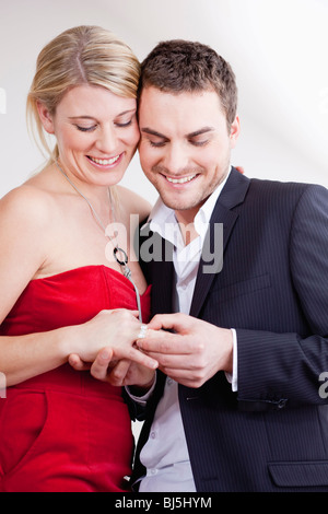 man putting ring on womans finger - Stock Photo